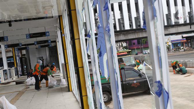 Petugas PPSU membersihkan sisa pecahan kaca di halte transjakarta Senen, Jakarta, Jumat (9/10/2020). Unjuk rasa menentang disahkannya Omnibus Law UU Cipta Kerja berujung aksi anarkis merusak berbagai fasilitas umum pada Kamis malam (8/10). (Liputan6.com/Helmi Fithriansyah)
