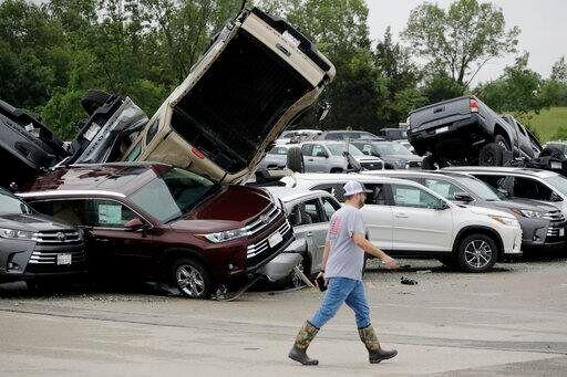 Worker pictured walking past damaged cars at a Toyota dealership in Jefferson City.