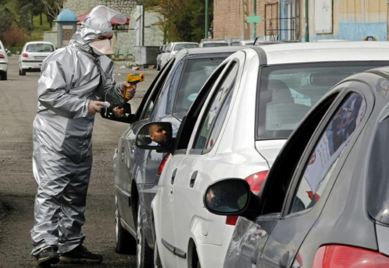 Members of the Iranian Red Crescent test people for coronavirus symptoms stopped on the Tehran to Alborz highway under a government order to screen every person for the illness