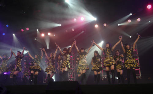 FILE - In this Feb. 25, 2012 file photo, members of JKT48, a sister group of Japanese idol group AKB48 perform during their joint concert in Jakarta, Indonesia. AKB48 is not exactly a band. It's an army of girls-next-door, ranked by its fans, and after taking Japan by storm it's getting ready to go global. JKT48, made up of Indonesian girls and young women, follows exactly the same routine as AKB. (AP Photo/Dita Alangkara, FIle)