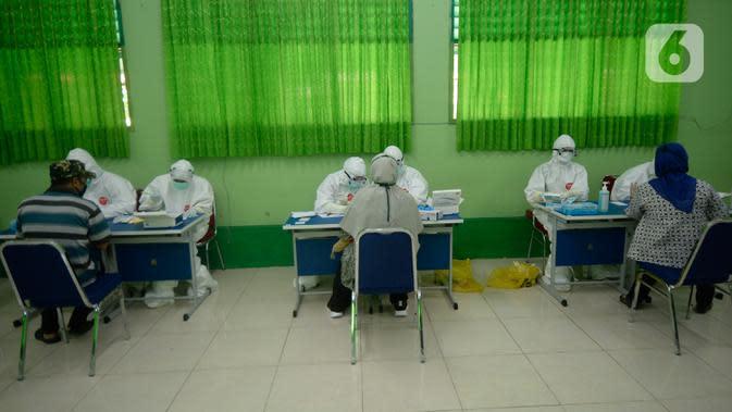 Petugas melakukan pemeriksaan cepat COVID-19 (Rapid Test) kepada tenaga pendidik SMP di SMPN 3 Ciputat, Tangerang Selatan, Kamis (27/08/2020). Rapid tes yang diikuti 400 guru mencakupi wilayah Ciputat dan Ciputat Timur itu untuk mencegah penyebaran Covid-19 di lingkungan pendidikan. (merdeka.com/Dwi