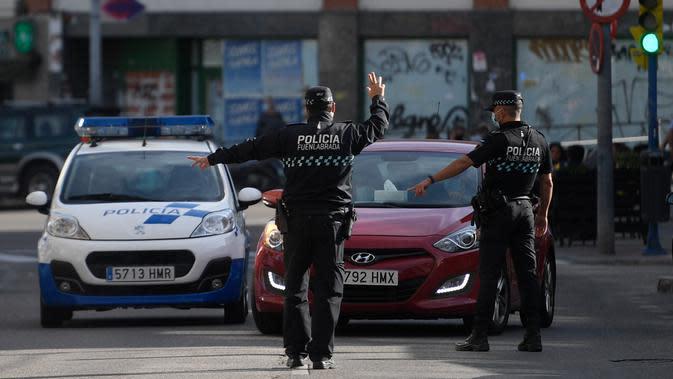 MADRID LOCKDOWN: Polisi setempat mengontrol pergerakan orang di sebuah pos pemeriksaan lalu lintas di kota Fuenlabrada yang tertutup sebagian, di wilayah Madrid (22/9/2020). Pemerintah daerah Madrid telah memberlakukan penguncian sebagian di beberapa daerah berpenduduk padat. (AFP/Oscar Del Pozo)