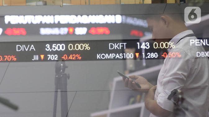 Pengunjung melintas dilayar pergerakan saham di BEI, Jakarta, Senin (30/12/2019). Pada penutupan IHSG 2019 ditutup melemah cukup signifikan 29,78 (0,47%) ke posisi 6.194.50. (Liputan6.com/Angga Yuniar)