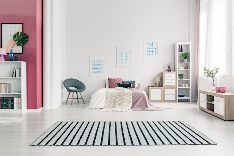small striped rug in white room with modern gray and purple furniture