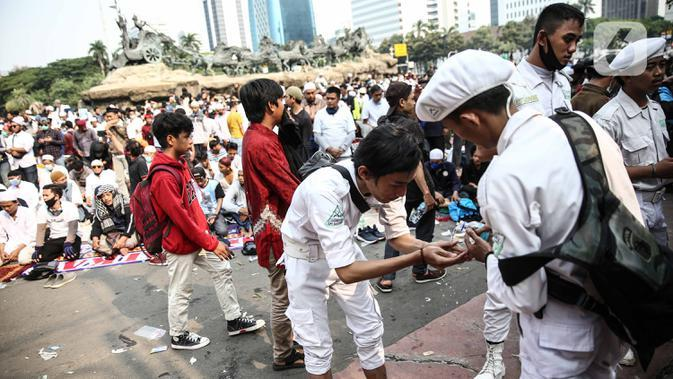 Massa aksi menggunakan air mineral untuk berwudhu sebelum salat Ashar di sela unjuk rasa di Kawasan Patung Kuda, Jakarta, Selasa (13/10/2020). Massa aksi menolak Undang-Undang Cipta Kerja Omnibus Law tersebut salat beralaskan spanduk, kardus, hingga sajadah. (Liputan6.com/Faizal Fanani)