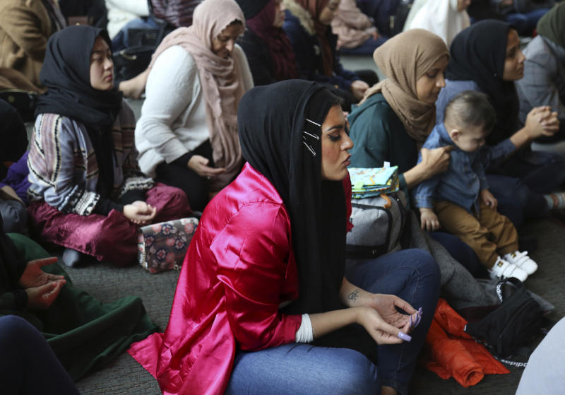 In this Dec. 27, 2019, photo, Amani Al-Khatahtbeh, center, sits near the back of the room at the Islamic Center of New York University during Friday prayers. At 17, she and a group of friends from her local mosque started the blog Muslimgirl.com in response to anti-Muslim bullying they experienced after 9/11. Ten years later, the blog has grown into an online magazine with a global audience. (AP Photo/Jessie Wardarski)