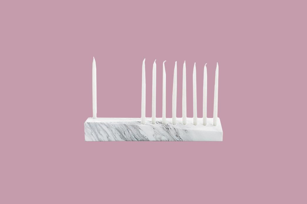 "<p>Not many menorahs can claim they hold a spot in the permanent collection at the <a href=""https://www.nmajh.org/"">National Museum of American Jewish History</a>, but such is the case for the Ascalon Menorah. Created by industrial designer Brad Ascalon, this elegant menorah is crafted of solid white Carrara marble and features facets for eight candles on one level that correspond to the eight days of Hanukkah, plus a ninth facet on another level for the shamash candle, which is used to light the rest.</p><p><em>Brad Ascalon's Ascalon Menorah, $275, </em><a href=""https://www.gopjn.com/t/8-9896-131940-110935?sid=MMSLHOLModernMenorahsCBiggsOct19&amp;url=https%3A%2F%2Fwww.dwr.com%2Faccessories-art-objects%2Fascalon-menorah%2F589611.html""><em>dwr.com</em></a><em>. </em></p>"