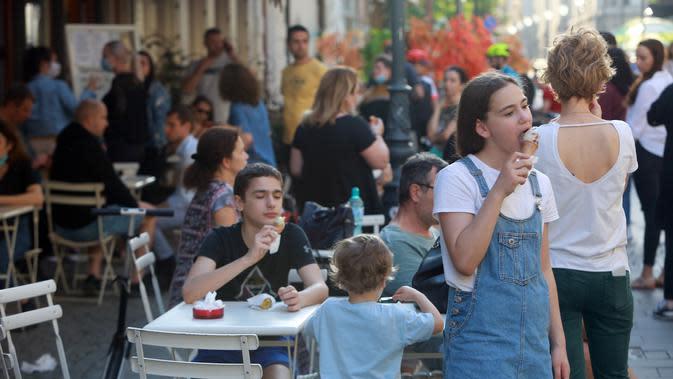 Warga mengunjungi sebuah kedai es krim di kota pusat sejarah Bucharest di Rumania pada 7 Juni 2020. Setelah dua tahap penerapan langkah pelonggaran, warga Rumania kini menjalani