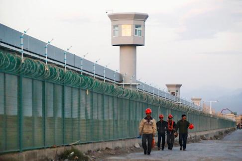 Workers walk by the perimeter fence of a government-run Uygur detainment camp in Dabancheng, Xinjiang, in 2018. Photo: Reuters