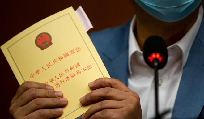 An opposition lawmaker holds up a copy of Hong Kong's Basic Law, the city's mini-constitution, during a news conference in April. Photo: Bloomberg