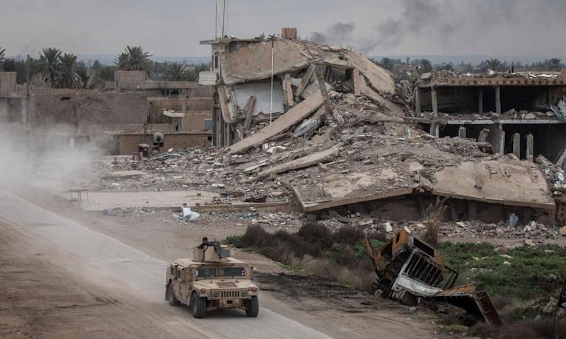 A military vehicle passes destroyed buildings in Baghouz, Syria