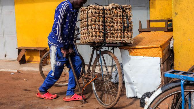 Seorang pria memompa ban sepedanya di Kampala, ibu kota Uganda (30/6/2020). Warga Uganda kini beralih menggunakan sepeda sebagai sarana transportasi yang mendukung di tengah pandemi COVID-19. (Xinhua/Hajarah Nalwadda)