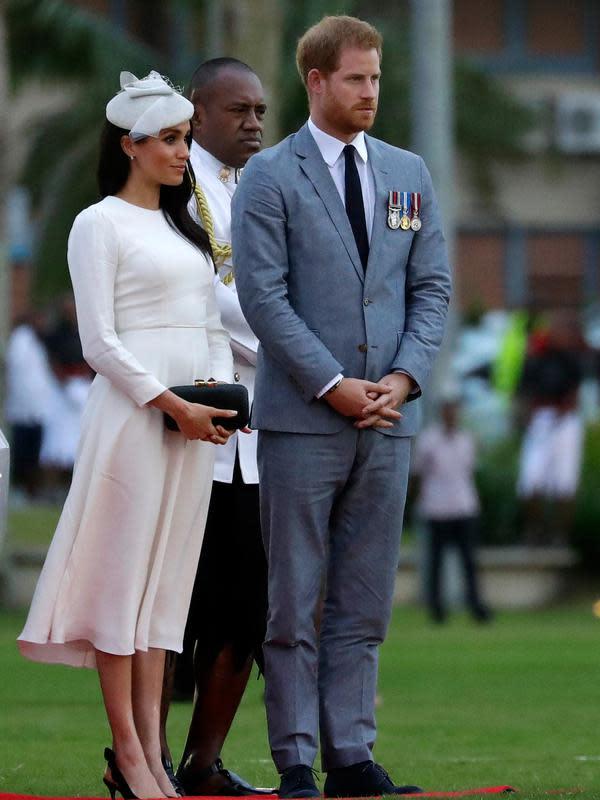 Pangeran Harry dan Meghan Markle saat menghadiri upacara penyambutan resmi di Suva, Fiji, Selasa (23/10. Berdasarkan aturan kerajaan, anak Pangeran Harry dan Meghan Markle adalah pewaris tahta ketujuh Kerajaan Inggris. (AP Photo/Kirsty Wigglesworth, Pool)