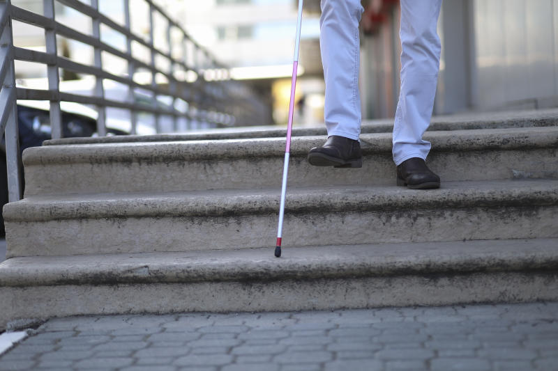 Close up of a young man with white support cane walking down the stairs.