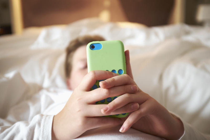 A teenage boy using an iPhone in bed. Two New Zealand parents have been fined after their boy refused to go to school and at one point missed 45 of 62 days.
