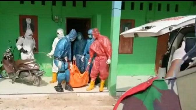 Penanganan jenazah pasien meninggal dengan status PDP di Sultra, memakai jas hujan karena kekurangan APD.(Liputan6.com/Ahmad Akbar Fua)