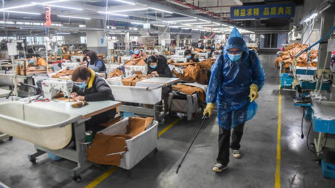 Pekerja menyemprotkan disinfektan di ruang produksi Hangzhou Jiefeng Garments Co. Ltd. di Hangzhou, Provinsi Zhejiang, China, Rabu (12/2/2020). Di bawah arahan dan dukungan otoritas setempat, banyak perusahaan di Zhejiang kembali beroperasi setelah melakukan pencegahan virus corona. (Xinhua/Xu Yu)