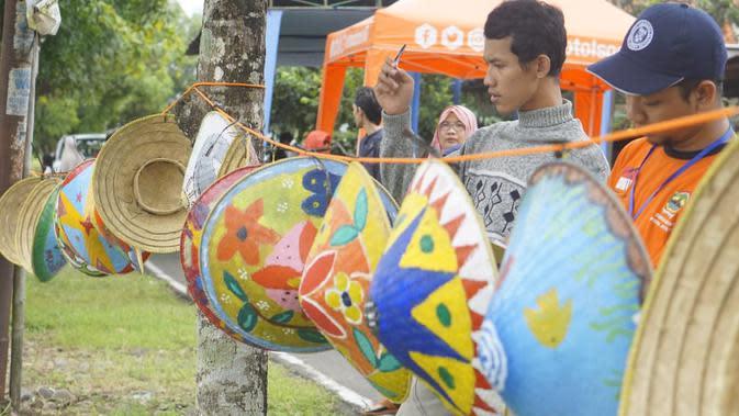 Tim juri lomba melukis caping menilai karya peserta yang dipajang di tepi sungai irigasi Kelurahan Toyareja, Kecamatan Purbalingga, Sabtu (11/1/2020). (Foto: Liputan6.com/Rudal Afgani)