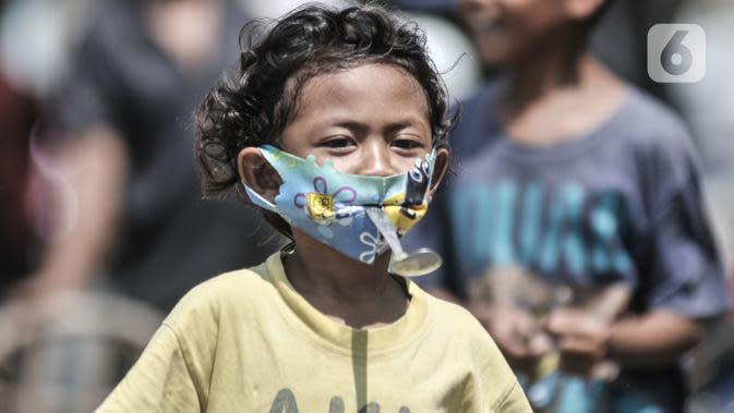 Seorang anak dengan masker mengikuti lomba memperingati HUT ke-75 RI di Kampung Nelayan, Cilincing, Jakarta, Senin (17/8/2020). Meski dilarang menggelar perlombaan akibat Covid-19, warga di Kampung Nelayan tetap mengadakan lomba 17-an walaupun hanya beberapa jenis. (merdeka.com/Iqbal Nugroho)