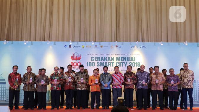 Menkominfo Johnny G. Plate berfoto bersama Wali Kota dan Kabupaten yang menerapkan konsep smart city di seluruh Indonesia dalam acara Gerakan Menuju 100 Smart City di Jakarta, Rabu (6/11/2019). (Liputan6.com/ Agustin Setyo W).