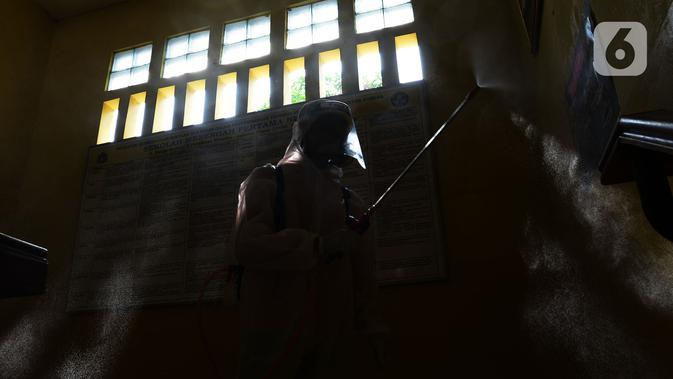 Petugas PMI menyemprotkan cairan disinfektan di Lingkungan SMP Negeri 139 Jakarta, Selasa (9/6/2020). Penyemprotan untuk mencegah penyebaran virus Corona di lingkungan sekolah itu sebagai persiapan memasuki tahun ajaran baru 2020/2021. (merdeka.com/Imam Buhori)
