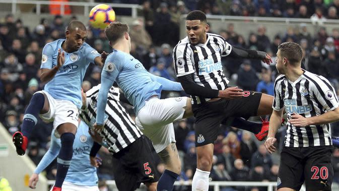 Pemain Newcastle United, Jamaal Lascelles, duel udara dengan bek Manchester City, John Stones, pada laga Premier League di Stadion James Park, Selasa (29/1). Newcastle United menang 2-1 atas Manchester City. (AP/Richard Sellers)
