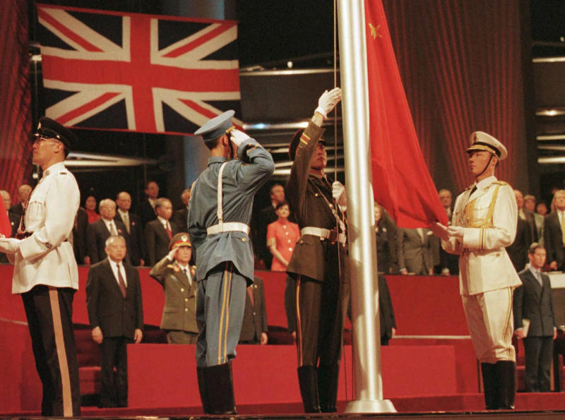 FILE - In this July 1, 1997, file photo, members of the combined Chinese Armed Forces raise the Chinese Flag at the Hong Kong convention center marking the moment Hong Kong reverted to Chinese rule. Hong Kong has been living on borrowed time ever since the British made it a colony nearly 180 years ago, and all the more so after Beijing took control in 1997, granting it autonomous status. A national security law approved by China's legislature on May 28, 2020 is a reminder that the city's special status is in the hands of Communist Party leaders who have spent decades building their own trade and financial centers to take Hong Kong's place. (Kimimasa Mayama/Pool Photo via AP)