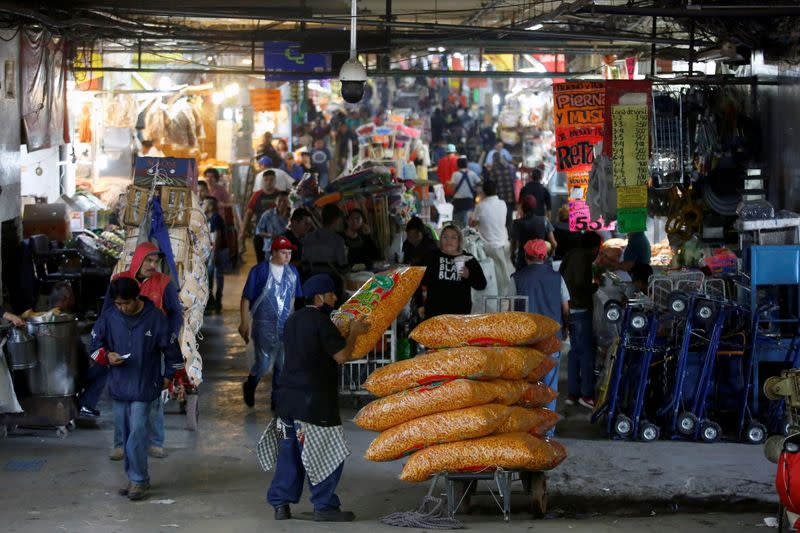 FILE PHOTO: A worker stacks bags of snack food in the Central de Abastos wholesale market in Mexico City