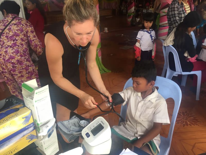 Jessica Manning uses a stethoscope on a healthy child in Chbar Mon, Kampong Speu Province