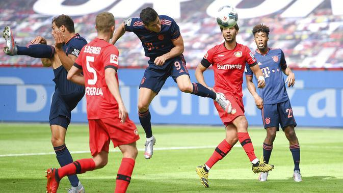Striker Bayern Munchen, Robert Lewandowski, mencetak gol ke gawang Bayer Leverkusen pada laga Bundesliga di BayArena, Sabtu (6/6/2020). Bayern Munchen menang 4-2 atas Bayer Leverkusen. (AP/Matthias Hangst)