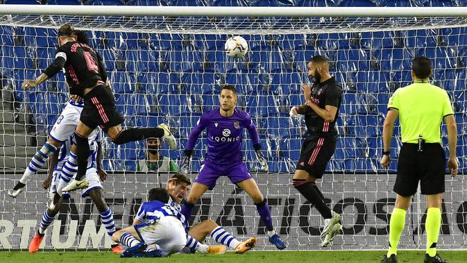 Bek Real Madrid, Sergio Ramos, menyundul bola saat melawan Real Sociedad pada laga Liga Spanyol di Stadion Anoeta, Minggu (20/9/2020). Kedua tim bermain imbang 0-0. (AP/Alvaro Barrientos)