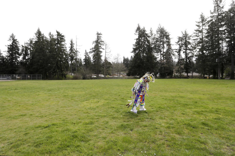 In this photo taken Saturday, April 4, 2020, Wakiyan Cuny, 16, a Dakota and Lakota tribal member, pauses in an open field as he prepares to dance during a live streamed powwow from a park near his home in Puyallup, Wash. The largest powwows in the country have been canceled or postponed amid the spread of the coronavirus. Tribal members have found a new outlet online with the Social Distance Powwow. They're sharing videos of colorful displays of culture and tradition that are at their essence meant to uplift people during difficult times. (AP Photo/Elaine Thompson)