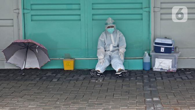 Tenaga kesehatan dengan APD menunggu warga yang akan melakukan tes swab di sekitar GSI Lab (Genomik Solidaritas Indonesia Laboratorium), Jakarta, Sabtu (3/10/2020). (Liputan6.com/Herman Zakharia)