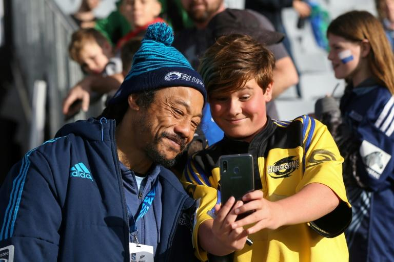 Auckland Blues assistant coach Tana Umaga poses for a selfie with a young fan before the Super Rugby match against Wellington Hurricanes at Eden Park