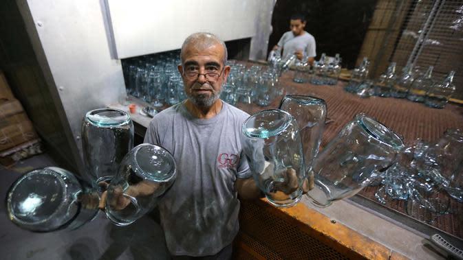Pekerja menunjukkan barang pecah belah di sebuah pabrik kaca di Tripoli, Lebanon, 12 September 2020. Kaca-kaca dari bangunan yang rusak akibat ledakan Beirut didaur ulang oleh warga setempat untuk dijadikan barang pecah belah. (Xinhua/Bilal Jawich)
