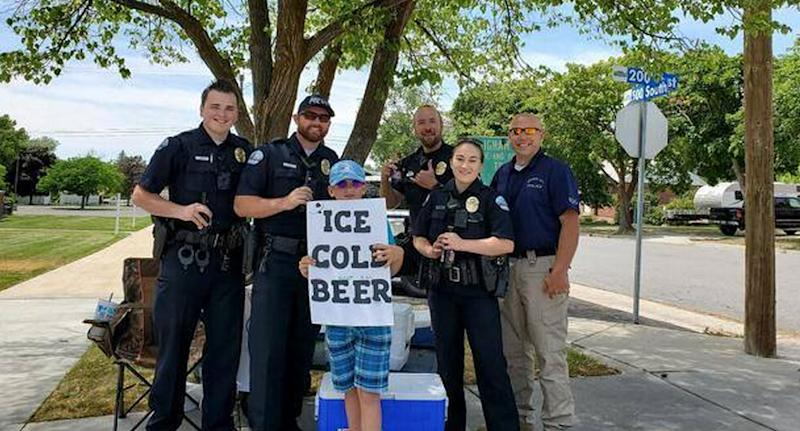 Photo of a young entrepreneur with local police who received reports he was selling beer on the street outside a church.