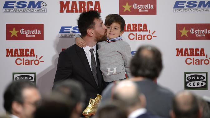 Lionel Messi mencium anaknya Thiago usai menerima penghargaan sepatu emas Europa pada Golden Shoe awards 2017 di Antigua Fabrica Estrella Damm, Barcelona, (24/11/2017). (AFP/Josep Lago)