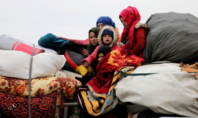 FILE PHOTO: Internally displaced Syrians from western Aleppo countryside, ride on a vehicle with belongings in Hazano near Idlib
