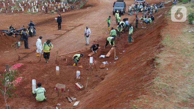 Petugas melakukan proses pemakaman jenazah dengan menerapkan protokol Covid-19 di TPU Pondok Ranggon, Jakarta Timur, Minggu (27/9/2020). Untuk tahap kedua, Dinas Bina Marga DKI Jakarta akan membuka lahan pemakaman baru seluas 6.150 meter persegi. (Liputan6.com/Herman Zakharia)