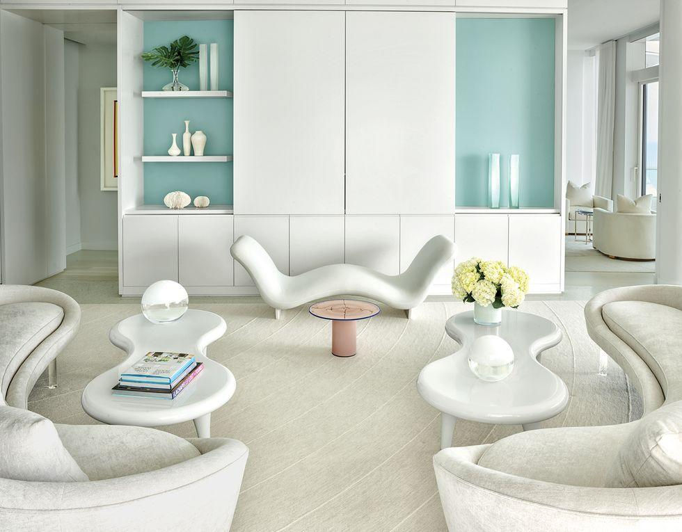 """<p>For a <a href=""""https://www.elledecor.com/design-decorate/house-interiors/a28816068/lee-mindel-miami-beach-house/"""" target=""""_blank"""">Miami Beach escape</a>, designer Lee F. Mindel settled on a seamless blend of modern touches and pop sensibilities—the perfect mix for a couple and their four children. The living room is outfitted with custom sofas in a Bergamo fabric, Marc Newson tables from Cappellini, and a 1980s side table by Vistosi. Mindel enhanced the design scheme with the eye-catching Face à Face bench by Pierre Paulin through Ralph Pucci, and a custom rug by V'Soske. The bookshelf, which is also custom, features a collection of vases and ceramics from Luminaire and Jalan Jalan. </p>"""