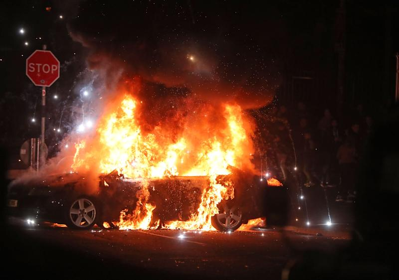 A car is set on fire after petrol bombs were thrown. Source AAP