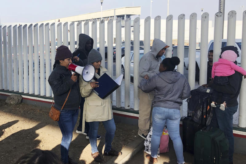 In this Nov. 12, 2019, photo, volunteers call names of people on a waiting list trying to obtain asylum in the United States along the U.S.-Mexico border in Tijuana, Mexico. The U.S. has sent a Honduran migrant back to Guatemala in a move that marked a new phase of President Donald Trump's immigration crackdown. (AP Photo/Elliot Spagat)