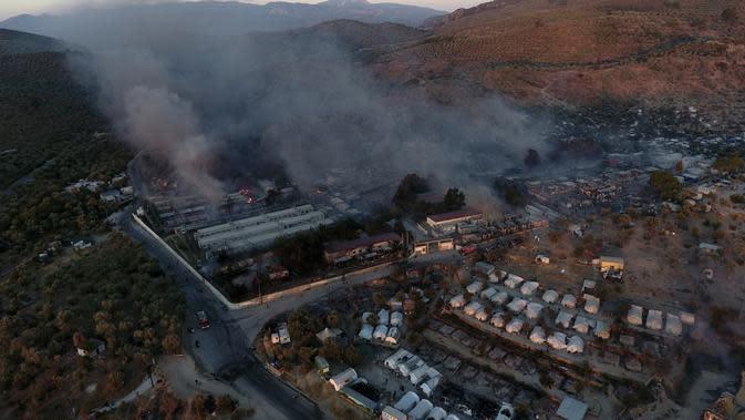 Api membakar rumah kontainer dan tenda di kamp pengungsi Moria di timur laut pulau Aegean Lesbos, Yunani, Rabu (9/9/2020). Sebanyak 25 petugas pemadam dengan 10 mesin dibantu polisi berupaya memadamkan api di dalam dan luar kamp pengungsi. (AP Photo/Panagiotis Balaskas)