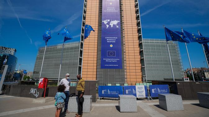 Orang-orang mengenakan masker terlihat di depan gedung kantor pusat Komisi Eropa di Brussel (18/5/2020). Belgia pada Senin (18/5) memasuki pelonggaran pembatasan tahap kedua dengan sekolah-sekolah membuka kembali beberapa kelas di bawah persyaratan organisasi yang ketat. (Xinhua/Zhang Cheng)