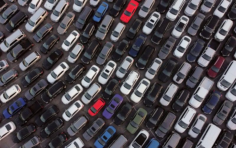 A photo taken with a drone shows rental cars sitting in a car park. - Shutterstock