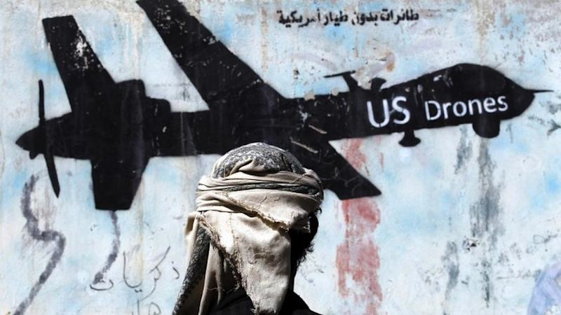 A Yemeni man stands in front of a graffiti depicting a drone, protesting against US military operations in war-affected Yemen,