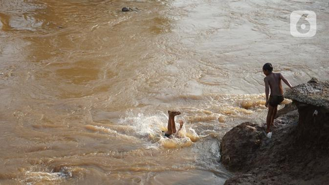 Anak-anak berenang di bantaran Sungai Ciliwung, Jakarta, Senin (5/10/2020). Derasnya aliran Sungai Ciliwung akibat hujan deras yang mengguyur Jakarta tidak menyurutkan kemauan anak-anak tersebut untuk tetap berenang, meski dapat membahayakan keselamatan mereka. (Liputan6.com/Immanuel Antonius)