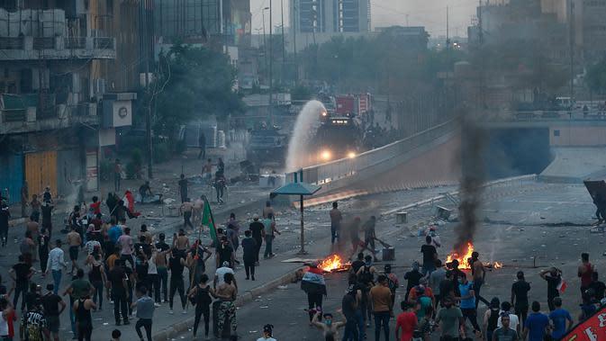 Pengunjuk rasa antipemerintah membakar sejumlah benda dan memblokir jalan saat menggelar protes di Baghdad, Irak, Rabu (2/10/2019). Aksi protes di seluruh Irak telah menewaskan sembilan orang dalam 24 jam. (AP Photo/Hadi Mizban)