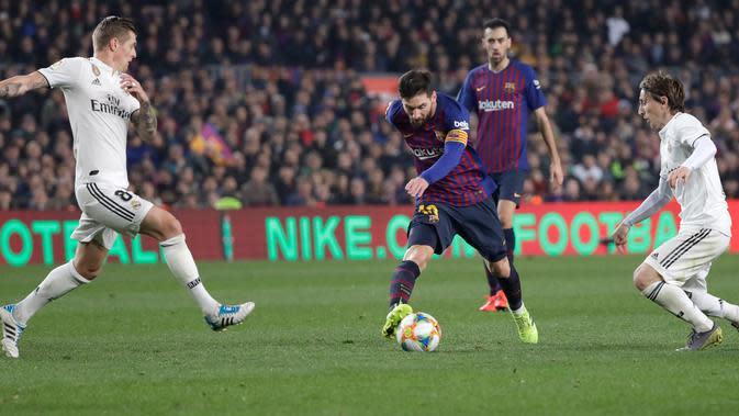 Penyerang Barcelona Lionel Messi (tengah) menggiring bola melewati pemain Real Madrid Toni Kroos dan Luka Modric saat bertanding pada leg pertama semifinal Copa del Rey di Stadion Camp Nou, Barcelona, Spanyol, Rabu (6/2). (AP Photo/Emilio Morenatti)