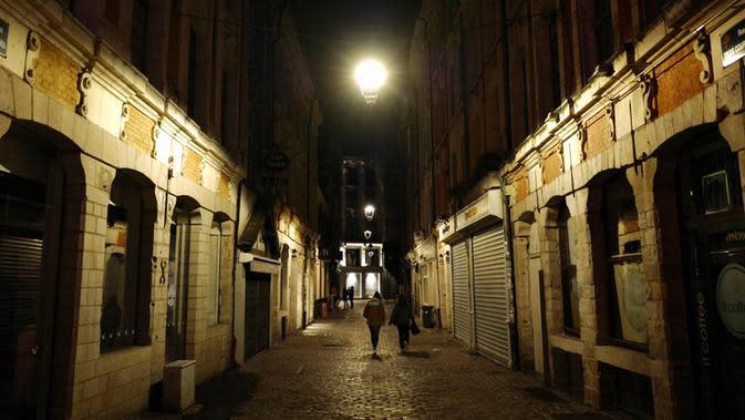 Orang-orang berjalan-jalan di Lille, Prancis, Jumat (16/10/2020). Prancis mengerahkan 12.000 polisi untuk memberlakukan jam malam baru mulai Jumat malam hingga bulan depan untuk memperlambat penyebaran COVID-19. (AP Photo/Michel Spingler)